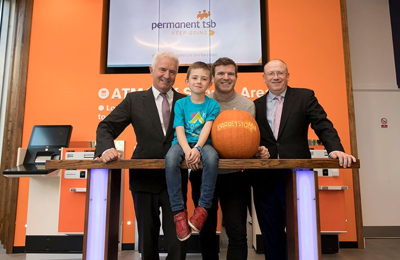 Three men standing behind a table with a child and pumpkin sitting on top of the table